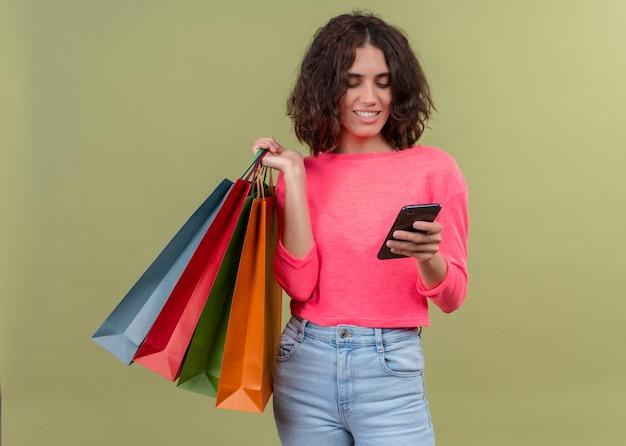Souriante jeune belle femme tenant des sacs en carton et téléphone mobile sur mur vert isolé