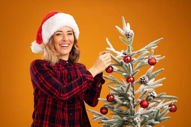 Souriante jeune belle fille debout à proximité d'arbre de noël portant un chapeau de noël décorer l'arbre de noël décorer l'arbre isolé sur fond orange
