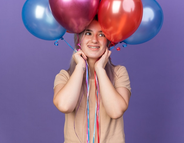 Souriante jeune belle fille portant des appareils dentaires tenant des ballons sur la tête isolés sur le mur bleu
