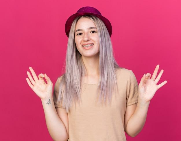 Souriante jeune belle fille portant un chapeau de fête avec des appareils dentaires faisant de la méditation