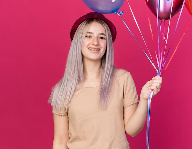 Souriante jeune belle fille portant un chapeau de fête avec des appareils dentaires tenant des ballons