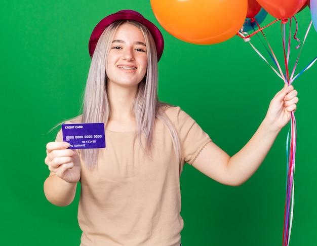 Souriante jeune belle fille portant un chapeau de fête et des bretelles tenant des ballons avec une carte de crédit