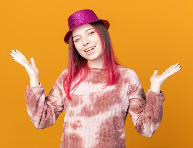 Souriante jeune belle fille portant un chapeau de fête écartant les mains