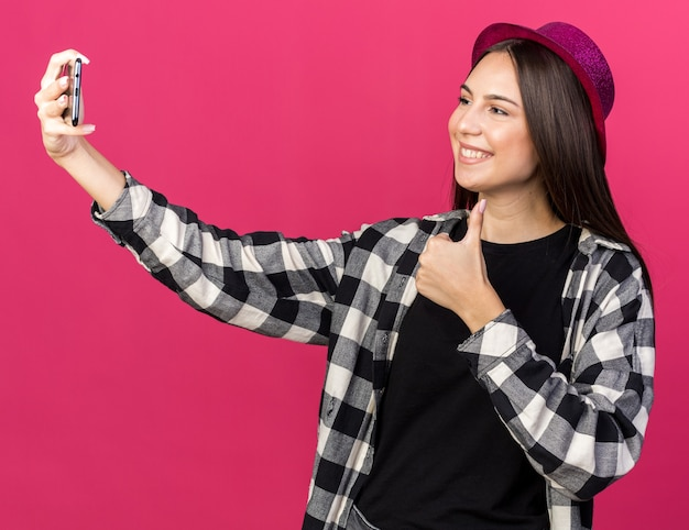 Souriante jeune belle fille portant un chapeau de fête prend un selfie montrant le pouce vers le haut isolé sur un mur rose