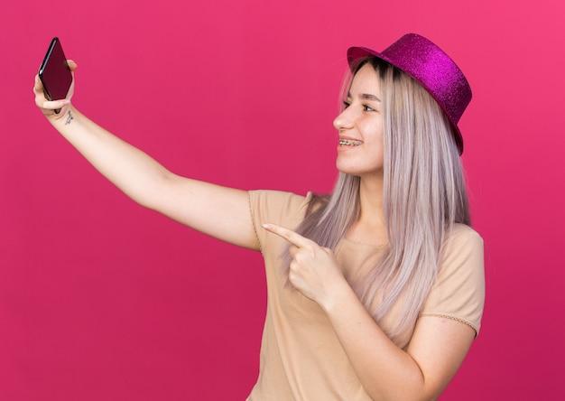 Souriante jeune belle fille portant un chapeau de fête prendre un selfie points au téléphone