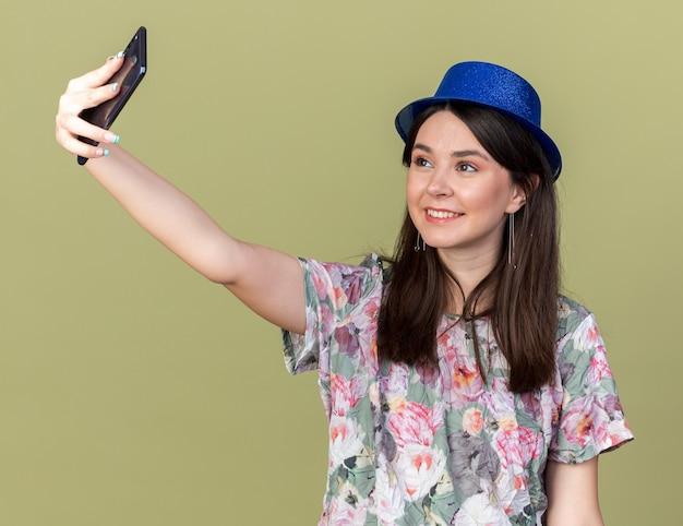 Souriante jeune belle fille portant un chapeau de fête prendre un selfie