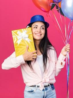 Souriante jeune belle fille portant un chapeau de fête tenant des ballons avec une boîte-cadeau