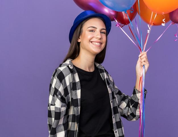 Souriante jeune belle fille portant un chapeau de fête tenant des ballons