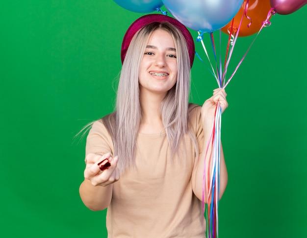 Souriante jeune belle fille portant un chapeau de fête tenant un sifflet de fête isolé sur un mur vert