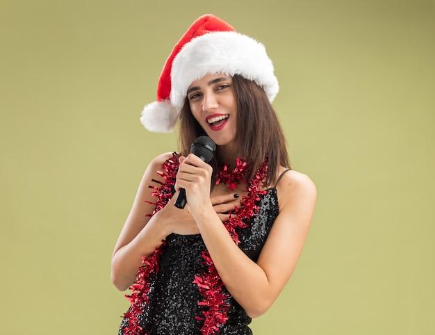 Souriante jeune belle fille portant un chapeau de noël avec une guirlande sur le cou tenant un microphone et chante en mettant la main sur elle-même isolée sur fond vert olive