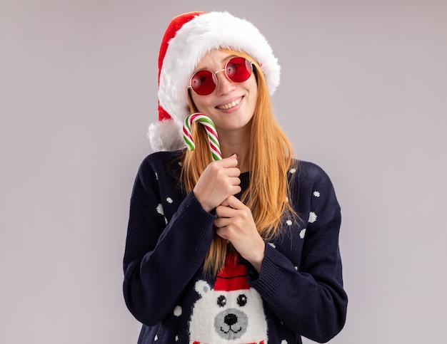 Souriante jeune belle fille portant un chapeau de noël et des lunettes tenant des bonbons de noël autour du visage isolé sur un mur blanc