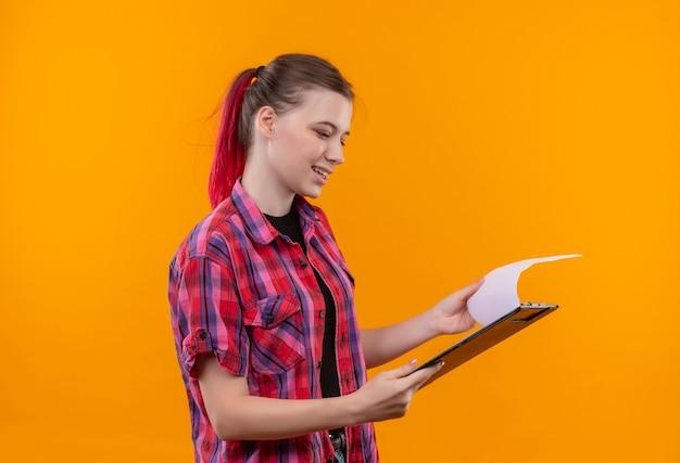 Souriante jeune belle fille portant une chemise rouge feuilletant le presse-papiers dans sa main sur fond jaune isolé