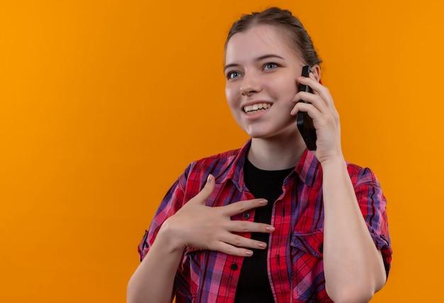 Souriante jeune belle fille portant une chemise rouge parle au téléphone sur fond jaune isolé avec espace de copie