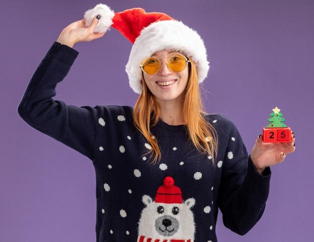 Souriante jeune belle fille portant un pull de noël et un chapeau avec des lunettes tenant un jouet de noël et un chapeau isolé sur un mur violet