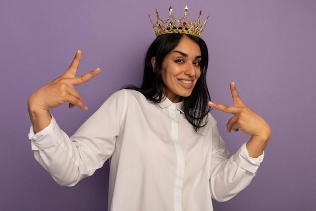 Souriante jeune belle fille portant un t-shirt blanc et une couronne montrant le geste de paix isolé sur violet