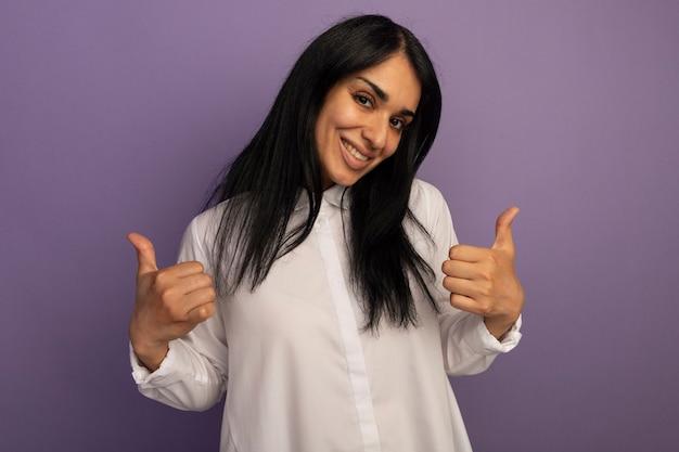 Souriante jeune belle fille portant un t-shirt blanc montrant les pouces vers le haut isolé sur violet