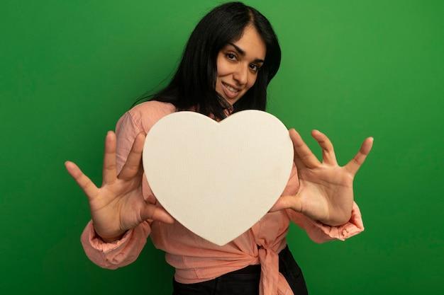 Souriante jeune belle fille portant un t-shirt rose tenant une boîte en forme de coeur isolé sur vert