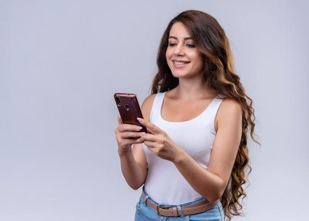 Souriante jeune belle fille tenant un téléphone mobile en le regardant avec espace de copie