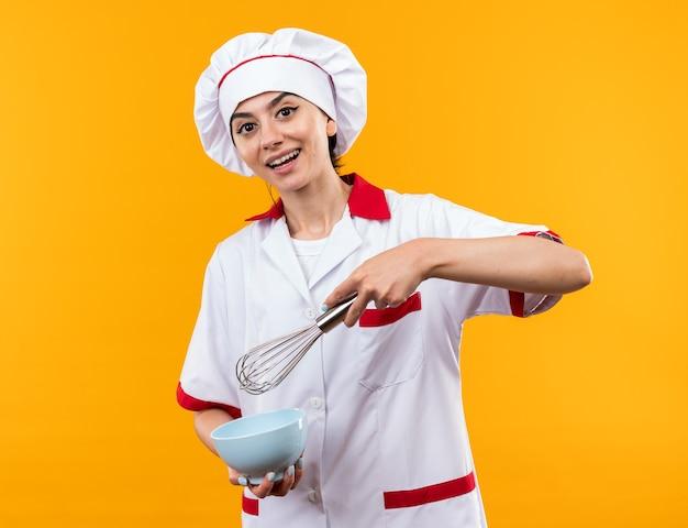 Souriante jeune belle fille en uniforme de chef tenant un bol avec un fouet isolé sur un mur orange