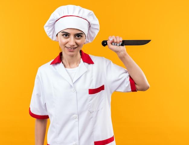 Souriante jeune belle fille en uniforme de chef tenant un couteau isolé sur un mur orange
