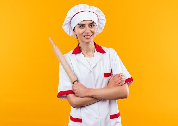 Souriante jeune belle fille en uniforme de chef tenant une goupille de rouleau traversant les mains isolées sur un mur orange