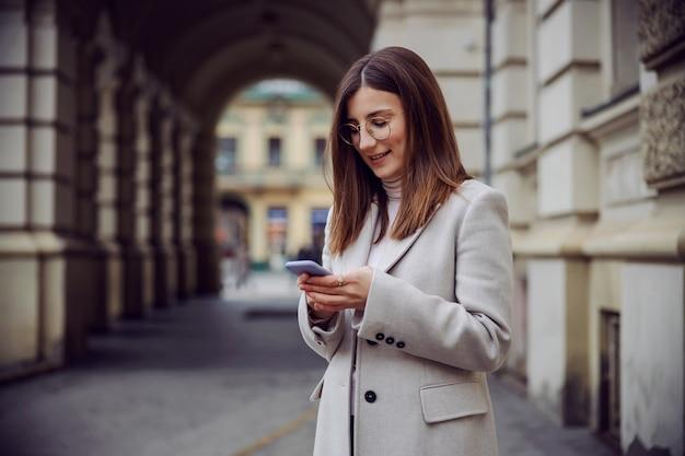 Souriante jeune brune debout dans la rue et utilisant le téléphone pour envoyer des sms ou accrocher sur les médias sociaux.