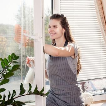 Souriante jeune brune nettoyant les vitres à l'aide d'un atomiseur d'intérieur
