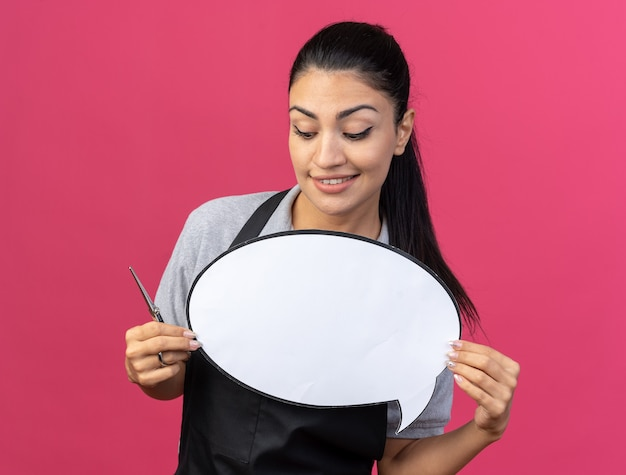 Souriante jeune coiffeuse caucasienne portant l'uniforme tenant et regardant la bulle de dialogue avec des ciseaux à la main isolé sur un mur rose