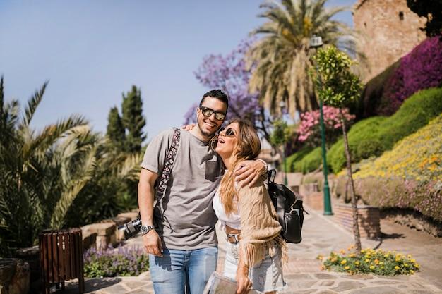 Souriante jeune couple debout dans le parc