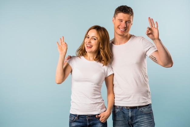 Souriante jeune couple montrant le geste de signe ok sur fond bleu