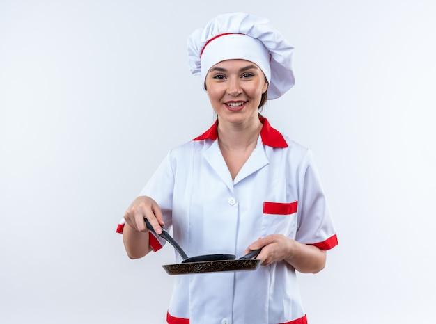 Souriante jeune cuisinière portant l'uniforme du chef tenant une poêle à frire avec une spatule isolée sur un mur blanc