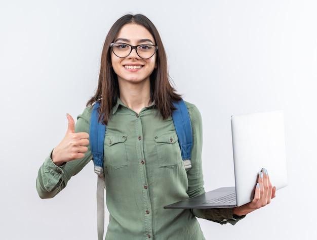 Souriante jeune écolière portant des lunettes avec sac à dos tenant un ordinateur portable montrant le pouce vers le haut