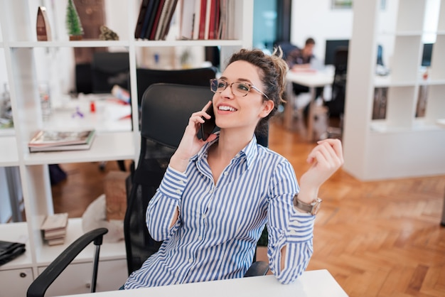 Souriante jeune employée de bureau parlant au téléphone.