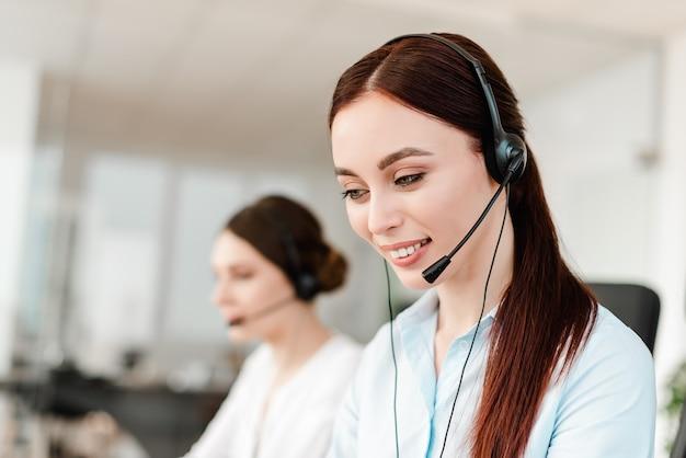 Souriante jeune employée avec un casque répondant dans un centre d'appels