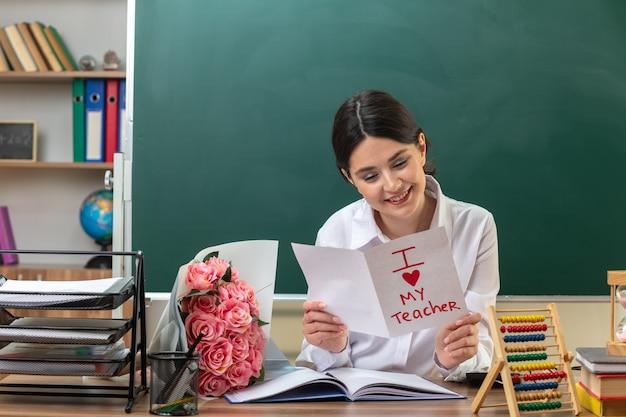 Souriante jeune enseignante tenant et lisant une carte de voeux assise à table avec des outils scolaires en classe