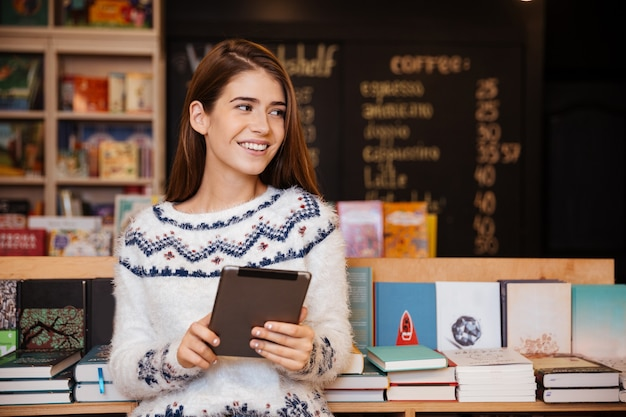 Souriante jeune étudiante à l'aide d'un ordinateur tablette dans une bibliothèque