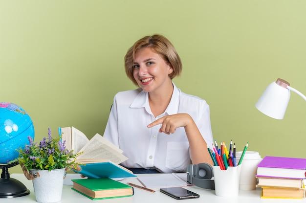 Souriante jeune étudiante blonde assise au bureau avec des outils scolaires tenant un livre ouvert pointant vers elle en regardant la caméra isolée sur un mur vert olive