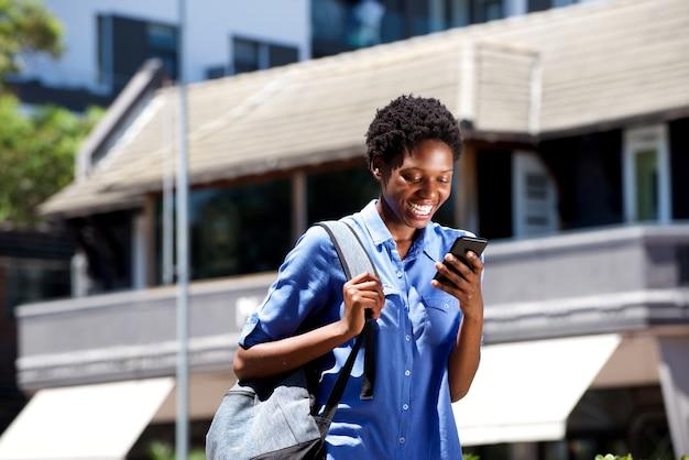 Souriante jeune étudiante marchant en plein air et lire des sms sur un téléphone intelligent