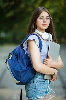 Souriante jeune étudiante avec sac à dos tenant un téléphone portable, marchant dans le parc, écoutant de la musique avec des écouteurs