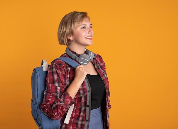 Souriante jeune étudiante slave avec des écouteurs portant un sac à dos se tient sur le côté