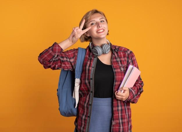 Souriante jeune étudiante slave avec des écouteurs portant un sac à dos tient un livre et un carnet de gestes signe de la main de la victoire