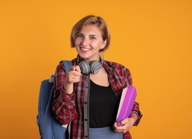 Souriante jeune étudiante slave avec des écouteurs portant un sac à dos tient un livre et un ordinateur portable à la caméra