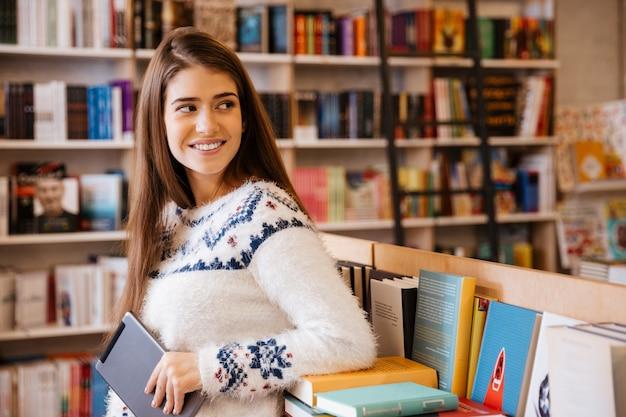 Souriante jeune étudiante tenant une tablette dans une bibliothèque