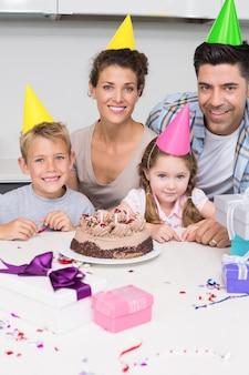 Souriante jeune famille célébrant un anniversaire ensemble