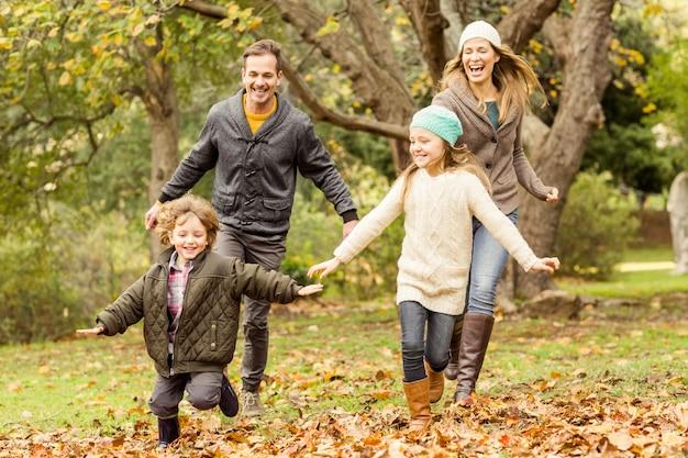 Souriante jeune famille courir dans les feuilles