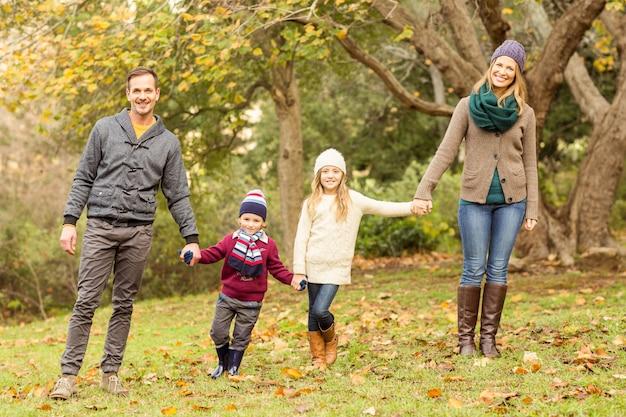Souriante jeune famille posant ensemble un jour d'automne