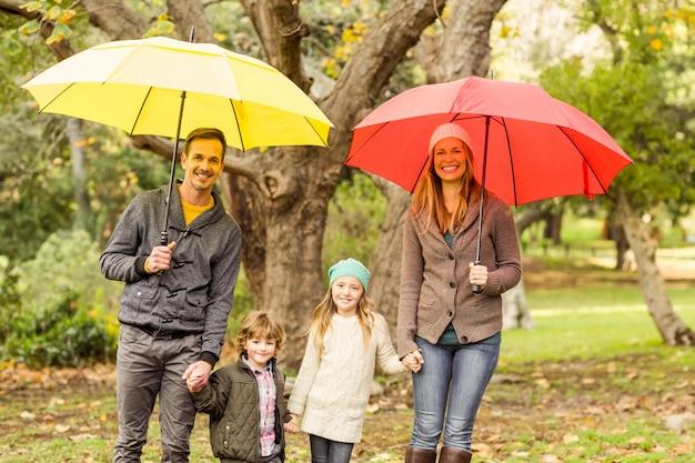 Souriante jeune famille sous le parapluie