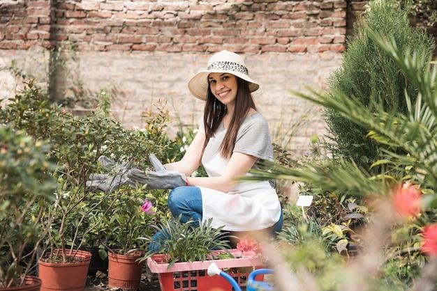 Souriante jeune femme accroupie dans une pépinière près des plantes