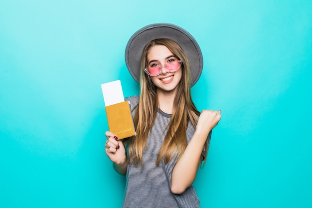 Souriante jeune femme adolescente détient ses documents de passeport avec billet dans ses mains isolé sur mur vert studio
