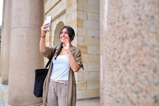 Souriante jeune femme adulte faisant un appel vidéo saluant avec la main à la caméra à l'extérieur d'un bâtiment